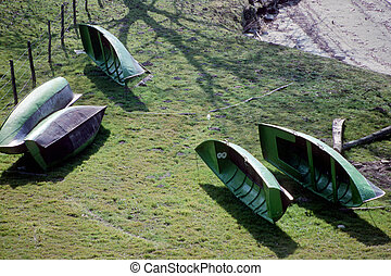 Green small boats on grass - Black and Green small boats on...