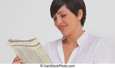 Businesswoman smiling while reading a newspaper against a...