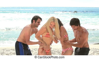 Two couples play and then hug each other while at the beach