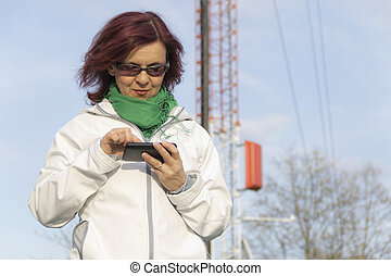 Good looking mid age woman with tablet phone under big...