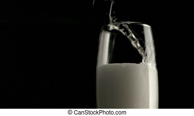 Champagne foam in a super slow motion filling a champagne flute glass