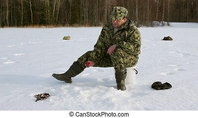 Ice Fishing - man fishing on the lake at winter