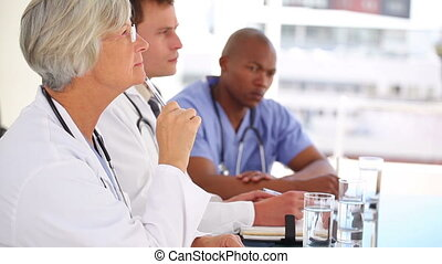 Serious doctor raising his finger to ask a question in a...