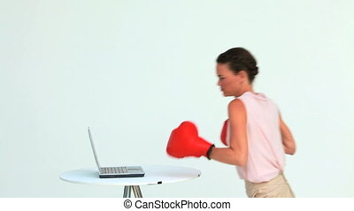 Businesswoman hitting a laptop with boxing gloves in studio