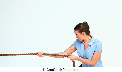 Woman in suit pulling a rope against white background