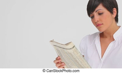 Businesswoman nods as she reads a newspaper against a grey...