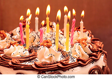 Birthday cake, lit candles on brown background.