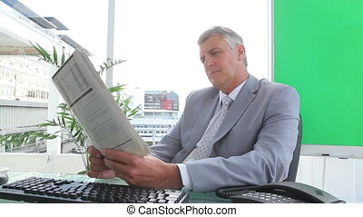 Businessman reading a newspaper in an office