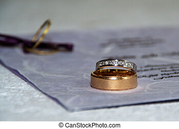 Rings and invitation - White and red gold rings laying on...