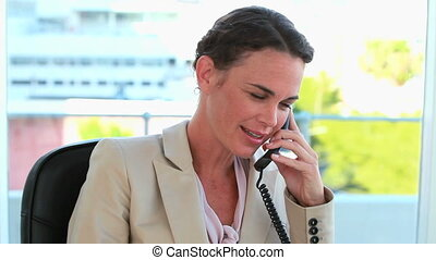 Well-dressed woman phoning in her office