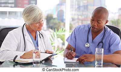 Nurse and doctor writing while working together in a bright...