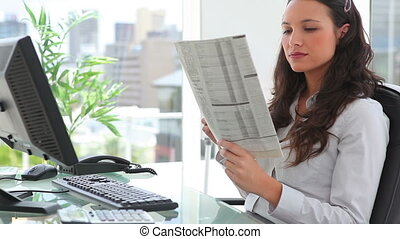 Businesswoman reading a newspaper in an office