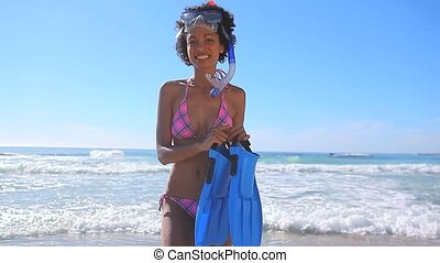 Cheerful brunette holding a snorkeling equipment on the...