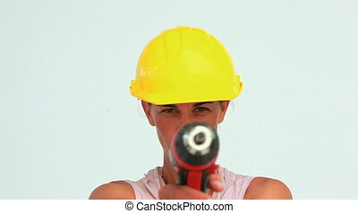 Woman wearing a safety helmet blowing on a screw gun against...