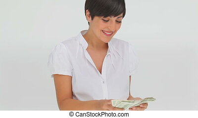 Businesswoman counting bank notes against a grey background