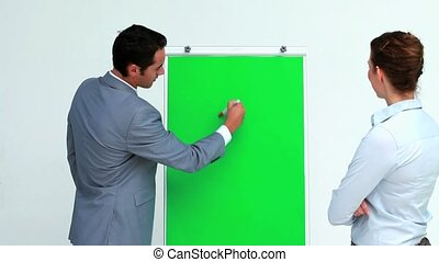 Man in suit explaining something on a board to a colleague...