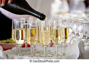champagne pour into glasses - a waiter pours champagne into...