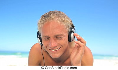 Blonde man bobbing while listening to music on the beach
