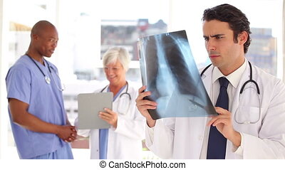 Smiling doctor looking at a chest x-ray