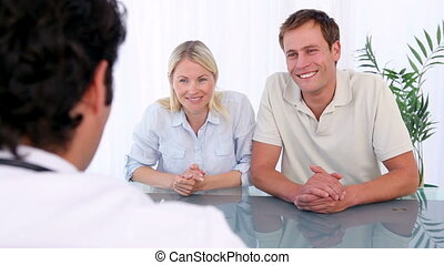 Happy couple talking with a doctor