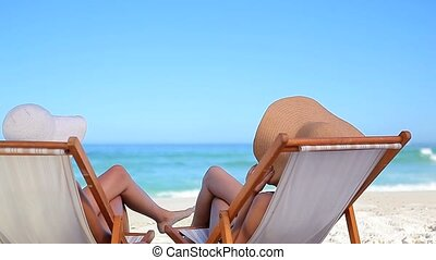 Peaceful woman resting while sitting on deck chairs on the...