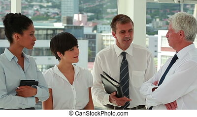 Business people talking while standing in a bright room