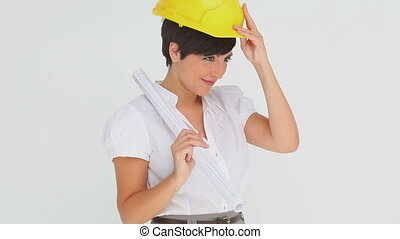 Businesswoman trying on a hard hat against a white...