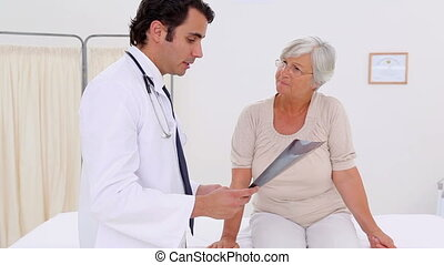 Serious doctor talking her patient about her x-ray in a...