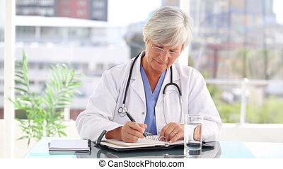 Serious mature doctor writing on her calendar in a bright...