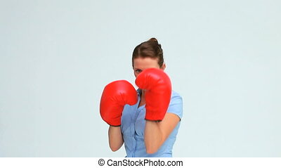 Businesswoman boxing in front of the camera against white...