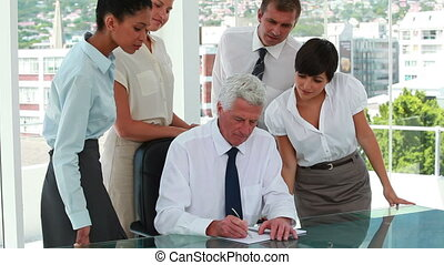 Business team around their boss who's writing on a file