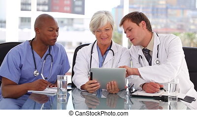 Serious medical team looking at a tablet computer in a...