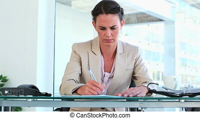 Woman in suit writing while sitting at her desk in a bright...
