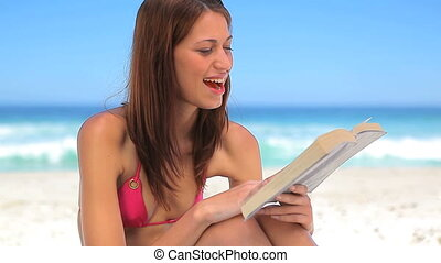 Smiling brunette reading a book while sitting on the beach