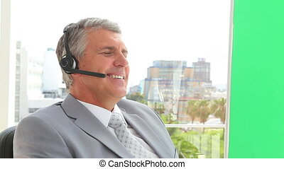Seated businessman talking on a headset in an office