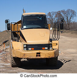 Dump truck waiting for a load - Yellow dump truck waiting...