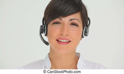 Businesswoman talking on a headset against a white...