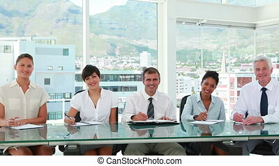 Business people applauding while sitting in a meeting room