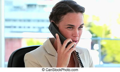 Businesswoman with tied hair on the phone in a bright office