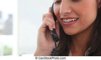 Brunette haired woman talking on the phone