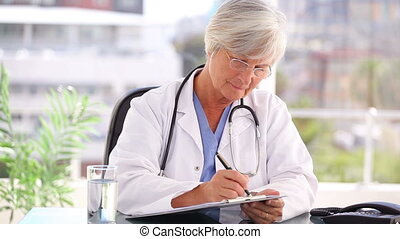 Serious mature doctor writing on her clipboard in a bright...