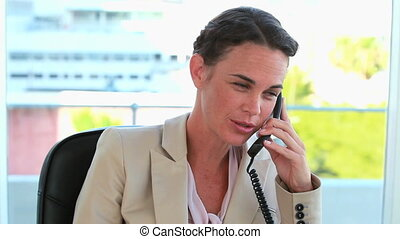 Businesswoman on the phone and looking at camera in a bright...