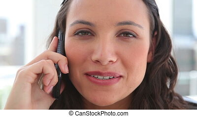 Businesswoman laughing during a phone call in an office