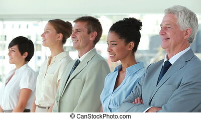 Business people in line looking away in a bright office