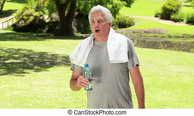 Happy mature man drinking water after doing sport in the...