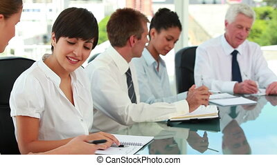 Business people at a meeting table talking with colleagues