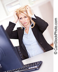 Stressful business woman working on computer