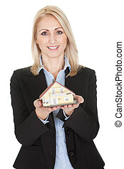 Businesswoman holding model of a house