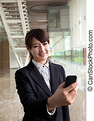 young businesswoman watching smart phone in hand