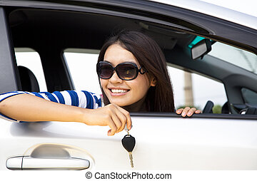 young woman holding key in car